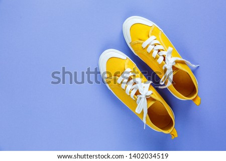 New pair of yellow sneakers on violet background with copy space. Lifestyle  sneaker sport shoe.