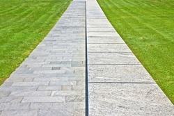 New paving ina public park made with stone blocks in a pedestrian zone and fresh green lawn - symmetrical and regular composition