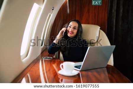 New perspectives. Front photo of an adorable girl in a casual outfit, who is enjoying her first-class flight, talking on the phone and looking through the window.