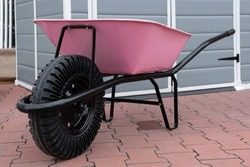 New Pink Garden wheelbarrow cart on backyard on farm, gardening tools