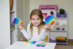 New popular silicone popit toy, baby is playing with it. Development of fine motor skills, like a puzzle