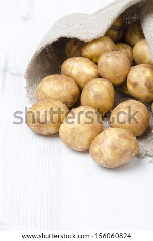 new potatoes in a sack on a white wooden board
