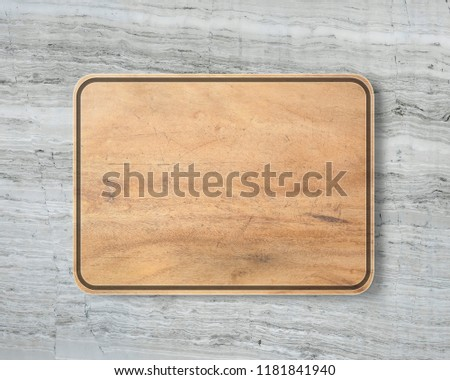 New rectangular wooden cutting board, top view on marble background