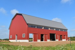 New red barn constructed on a farm in summer with doors open