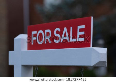 New red sign for sale in front of house in residential area. Real estate bubble, bidding war, hot housing market, overpriced property, buyer activity, spring and summer sale  concept. Selective focus. stock photo