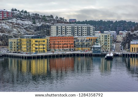 New residential apartment blocks sit on a hillside near the waterfront of Baltic sea bay in the Kvarnholmen district of Stockholm, Sweden at overcast winter morning.