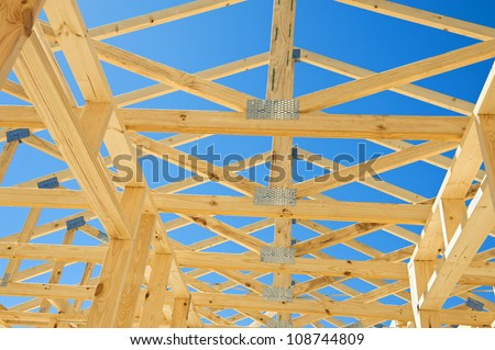 New residential construction home framing against a blue sky.