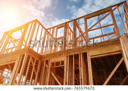New residential construction home framing against a blue sky. Roofing construction. Wooden construction #765579673