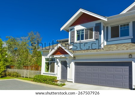 New residential townhouse on sunny day with wide garage door and concrete pathway in front. British Columbia, Canada.
