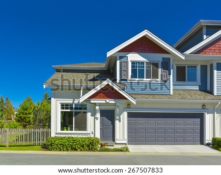 New residential townhouse with entrance and garage doors in front on sunny day, British Columbia, Canada. Garage with concrete driveway and asphalt road in front.