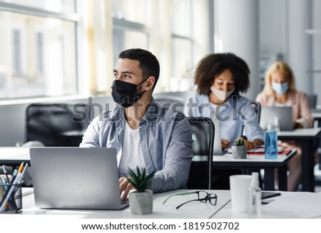 New rules for working in office and create a new idea. Arabian guy in protective mask looks out the window and works at laptop at workplace with antiseptic and flower in pot, free space