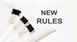 NEW RULES written on white page with office tools