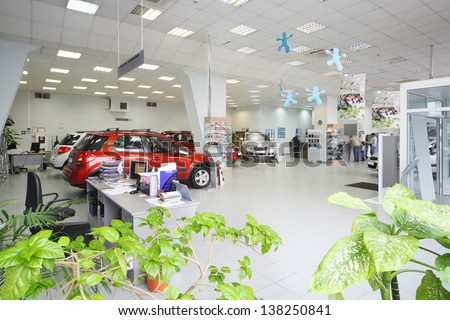 New shine cars stand in big office of shop selling cars near tables with computers.
