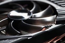 New shiny black plastic GPU cooler, close-up photo with selective focus. This fan is mounted on a video card to cool the GPU