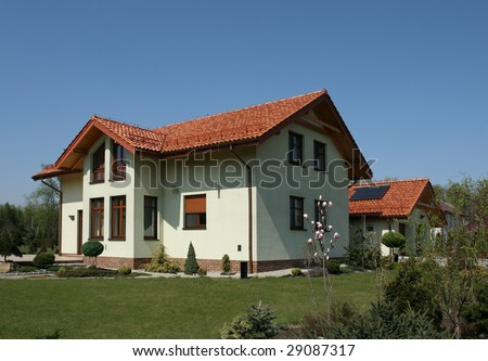 New single family home with red slate roof and garden