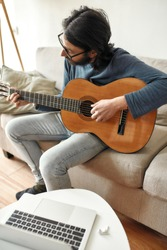 New skill. Young focused man sitting on sofa at home and playing acoustic guitar, watching online music course on laptop and practicing chords. Distance education. Focus on man. Stay home. E-learning