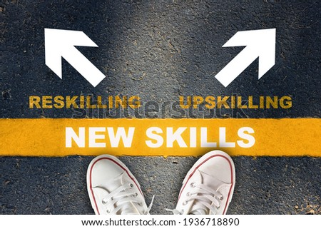 New skills development concept and changing skill demand idea. New skills written on yellow line with reskilling and upskilling with white arrow on asphalt road