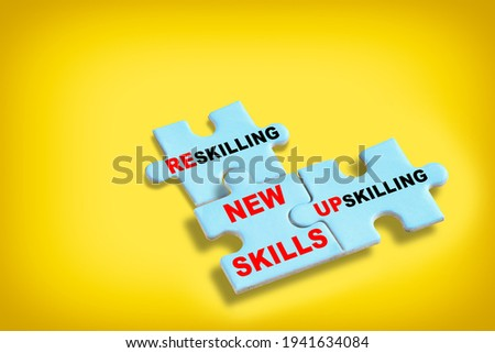 New skills development concept and changing skill demand idea. Reskilling, up skilling and new skills written on blue puzzle isolated on yellow background