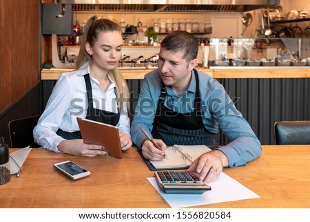 New small business owners counting revenue and expenses - Start-up entrepreneurs, woman and man, businessmen doing accounting with calculator and tablet in Restaurant