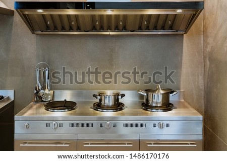 New stainless gas stoves cabinet with oversized cooker hood inside an industrial kitchen. #1486170176
