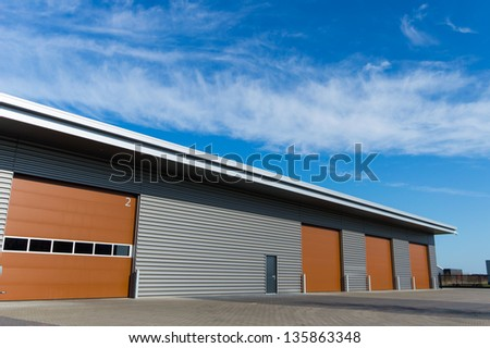 new storage warehouse with brown doors and blue sky