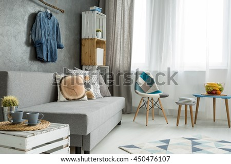 New style flat in grey with sofa, small table, chair, pattern carpet and beautiful home decorations
