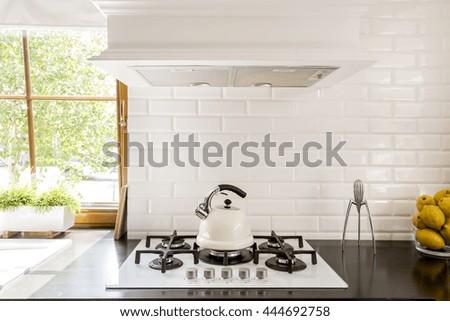New style kitchen with dark worktop, white gas cooker and decorative brick backsplash