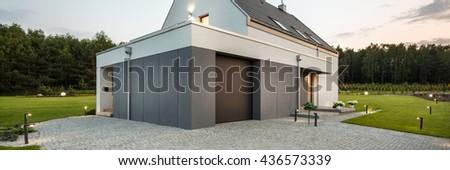 New style white villa with stone driveway, decorative lighting and wide backyard, panorama