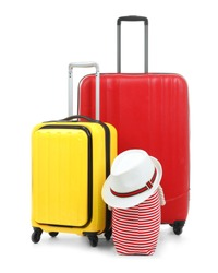 New suitcases, bag and hat packed for journey on white background