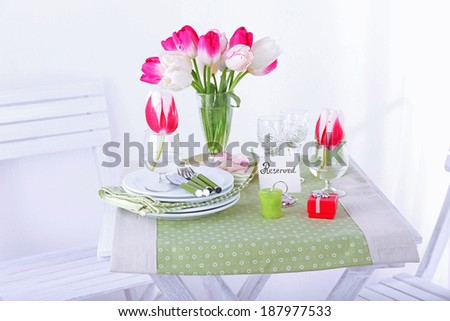 New table and chairs with place settings on light background