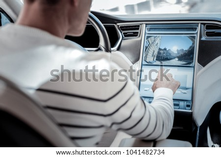 New technology. Nice pleasant man sitting in his car and pressing a button on the control panel while starting to drive #1041482734