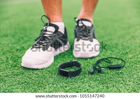 New technology sport wearable accessories for runners: fitness sports smart watch and wireless earphones man running shoes. Earbuds, smartwatch on grass. Tech run gear, smart jogging.