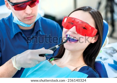 New teeth and a perfect smile. Smiling dentist fixes the dental filling UV lamp while smiling patient sitting in the dental chair and smiling widely.