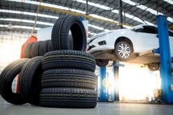 new tires that change tires in the auto repair service center, blurred background, the background is a new car in the stock blur for the industry, a four-wheeled tire set at a large warehouse