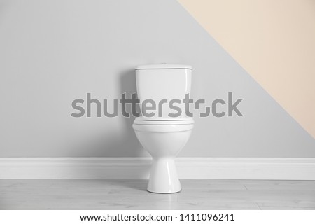 New toilet bowl near color wall indoors #1411096241