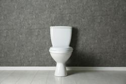New toilet bowl near grey wall indoors