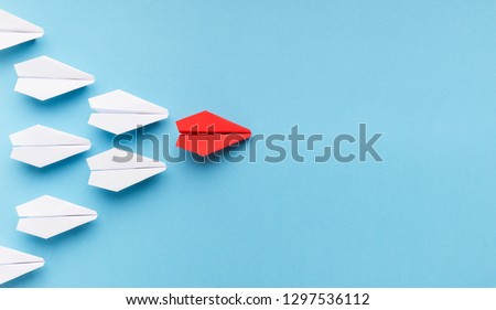 New trends concept. One red paper plane followed by group of white ones on blue background, copy space Foto d'archivio ©