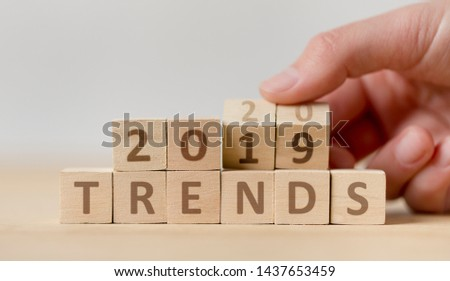 New trends concept. Woman hand turning over wooden blocks with text from 2019 to 2020 on background, panorama #1437653459