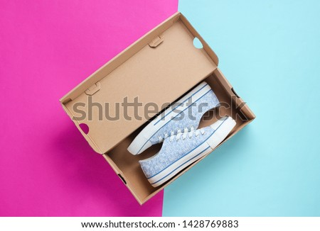 New trendy sneakers in cardboard box on colored background. Top view