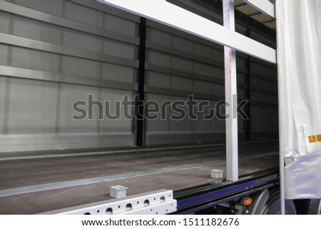 New truck empty semi trailer with removable curtains, indoor side view close-up, lorry transportation logistics with side loading #1511182676