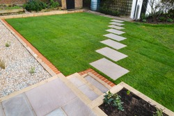 New turf installed around a stepping stone pathway in a garden or back yard.
