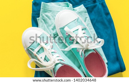 New turquoise sneakers on yellow background with copy space. White blue pink cross laces. Jeans celadon style. #1402034648