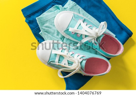 New turquoise sneakers on yellow background with copy space. White blue pink cross laces. Jeans celadon style. #1404076769