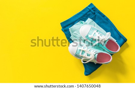 New turquoise sneakers on yellow background with copy space. White blue pink cross laces. Jeans celadon style. #1407650048