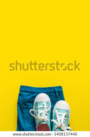 New turquoise sneakers on yellow background with copy space. White blue pink cross laces. Jeans celadon style. #1408137440