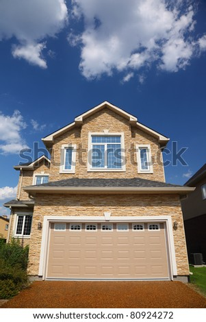 New two-storied beige stone cottage with garage in front of it.