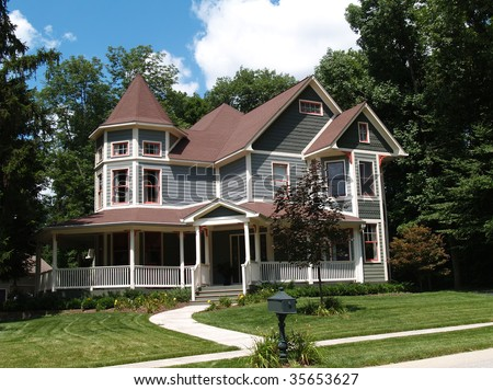 New two story Victorian residential home with vinyl or board siding on the facade styled after an old-fashioned historical house with bay windows, gingerbread and a turret.