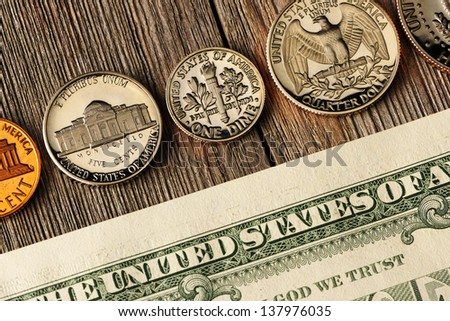 New uncirculated US money over wooden background - stock photo