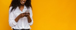 New useful application. Black woman using cellphone on yellow background, free space