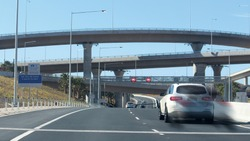 New westconnex motorway and over passes. A blurred white car travelling on the road. 80km speed limit signs. Australian city road.